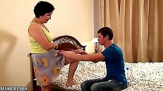 Mature dark haired woman with big tits is having sex with a much younger guys