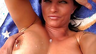 Busty brunette MILF oils up her hot tits