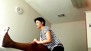 Mature Asian masseuse strokes him to an orgasm
